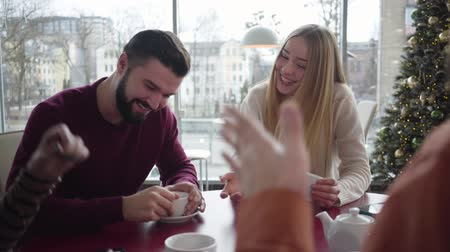 chlapík : Portrait of positive young Caucasian boyfriend and girlfriend talking about vacations with couple of friends. Happy soulmates meeting fellows in cafe. Memories, happiness, lifestyle. Dostupné videozáznamy