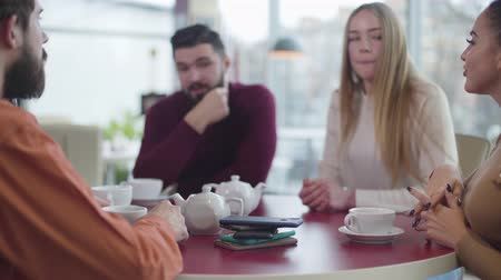 obsession : Close-up of smartphones lying on the table in cafe as group of young friends chatting at the background. Happy people spending time without gadgets in restaurant. Digital addiction, lifestyle. Stock Footage