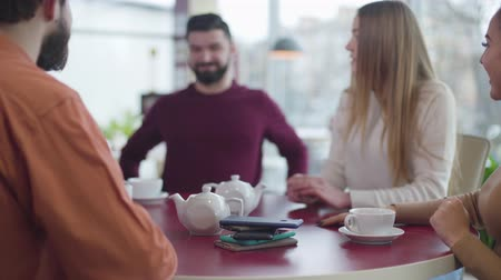 obsession : Blurred Caucasian man stretching to phone lying at the foreground and taking his hand back quickly. Group of Caucasian friends meeting without devices in cafe. Addiction, digitalization, lifestyle. Stock Footage