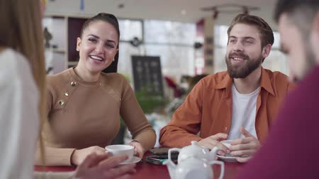 четыре человека : Happy young Caucasian couple talking with friends in restaurant. Cheerful man and woman resting in cafe with fellows. Youth, lifestyle, joy, happiness.