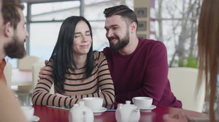 chlapík : Portrait of young Caucasian couple in love hugging in cafe. Happy man and woman sitting with friends in restaurant on weekends. Lifestyle, joy, happiness, leisure.
