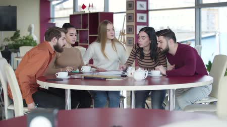 chlapík : Group of positive young university students coming to the table, sitting down and discussing project. Teamwork of friendly adult groupmates in cafe. Education, intelligence, lifestyle, friendship.