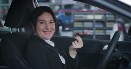 car dealership : Close-up of smiling Caucasian businesswoman turning to camera and showing keys from new vehicle. Satisfied female customer buying car in showroom. Automobile industry, wealth. Cinema 4k ProRes HQ.