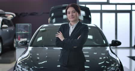 sala de exposição : Portrait of adult successful female car dealer posing in dealership. Caucasian brunette woman crossing hands and looking at camera in front of new automobile. Industry, trading. Cinema 4k proRes HQ.