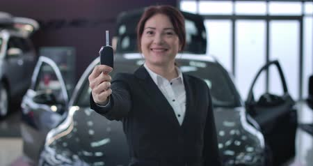 трейдер : Close-up of positive Caucasian woman showing car keys at camera. Focus changes from face of female trader to keys. Professional dealer posing in auto showroom. Cinema 4k ProRes HQ. Стоковые видеозаписи