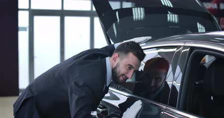 sala de exposição : Close-up side view of positive Caucasian man in suit and white gloves touching new car in showroom. Young male dealer examining new vehicle in dealership. Automobile industry. Cinema 4k ProRes HQ.