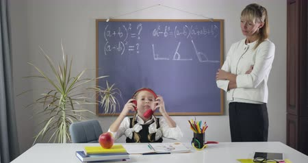 репетитор : Shocked Caucasian teacher watching ad schoolgirl putting on headphones and shaking head. Cheerful little girl misbehaving as studying at home. Education, learning. Cinema 4k ProRes HQ.