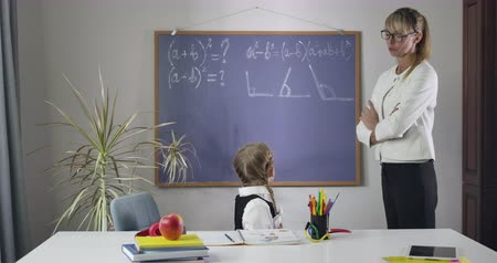 diligence : Cute Caucasian schoolgirl looking back at blackboard, turning back to camera and putting head on hands. Middle aged woman teaching math to tired child. Intelligence, education. Cinema 4k ProRes HQ.