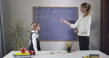 elsődleges : Portrait of smart Caucasian woman explaining math to cute little girl. Tutor pointing at geometrical formulas written on blackboard and talking. Teaching, education concept. Cinema 4k Prores HQ.