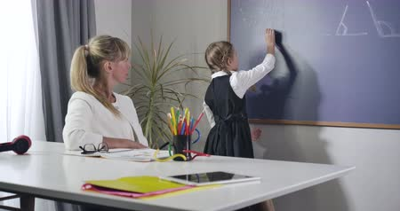 diligence : Diligent Caucasian schoolgirl turning to blackboard and writing with chalk. Adult woman sitting at the table and teaching child. Education, elementary student. Cinema 4k ProRes HQ.