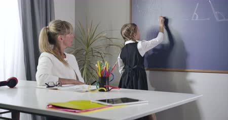 diligence : Portrait of adult Caucasian teacher dictating formula to little girl writing on blackboard. Middleaged tutor teaching child at home. Elementary education, diligence, intelligence. Cinema 4k ProRes HQ.