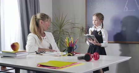 diligence : Charming Caucasian girl in school uniform declaiming to middle aged teacher sitting at the table. Intelligent child studying at home. Private teaching, tutoring, education. Cinema 4k ProRes HQ. Stock Footage