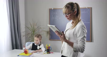 репетитор : Portrait of adult Caucasian woman standing with tablet as little pretty schoolgirl writing in exercise book. Child looking up and putting head on hands. Intelligence, education. Cinema 4k ProRes HQ.