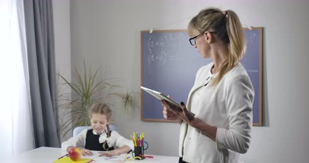 diligence : Caucasian schoolgirl making i got an idea gesture and writing down in exercise book. Middle aged woman standing at the foreground and looking back at child. Focused on teacher. Cinema 4k ProRes HQ.