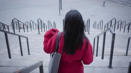 kahve molası : Back view of elegant young lady in red coat walking down the stairs. Confident Caucasian woman with black hair strolling in city in autumn day holding coffee cup. Lifestyle, break, leisure. Stok Video