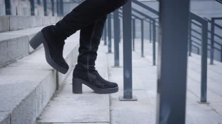 nőiesség : Camera following female legs in high boots walking down the stairs. Woman strolling in city. Lifestyle, leisure. Stock mozgókép
