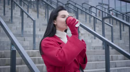 kahve molası : Profile portrait of charming Caucasian lady in red coat and gloves drinking coffee in city. Young cheerful woman standing on stairs outdoors and having break. Lifestyle, coffee break, leisure.