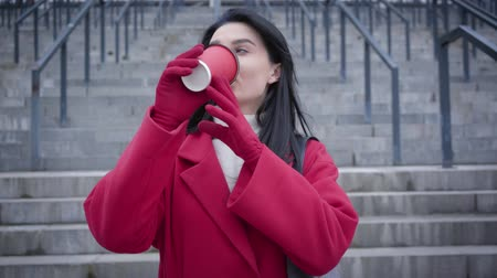 kahve molası : Portrait of cheerful young woman drinking coffee and stretching cup to camera. Positive pretty girl in red coat and gloves having break outdoors. Leisure, lifestyle, urban life. Stok Video