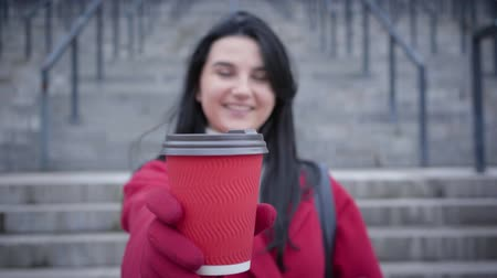 kahve molası : Unrecognizable blurred Caucasian woman stretching coffee cup to camera and smiling. Young lady in red coat and gloves enjoying break on stairs in city. Urban life, lifestyle. Focused on cup.