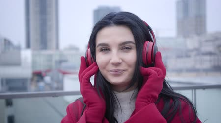 plezant : Close-up face of smiling young Caucasian girl with black hair and green eyes putting on earphones in city. Cheerful cute woman listening to music outdoors. Lifestyle, beauty, hobby.