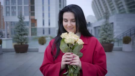 egyetlen virág : Portrait of romantic young Caucasian woman smelling yellow roses and looking at camera. Fashionable lady with black hair dressed in red coat posing in city in autumn day. Joy, happiness, lifestyle.