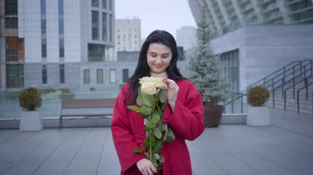 egyetlen virág : Camera approaching to happy young lady smelling yellow roses under light rain in city. Beautiful Caucasian woman holding bouquet of flowers and smiling. Joy, happiness, lifestyle. Stock mozgókép