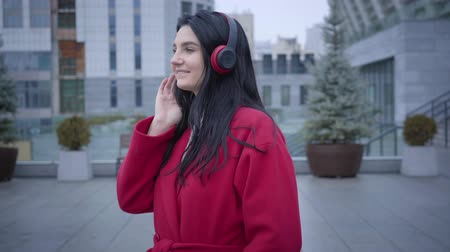 plezant : Portrait of young cheerful Caucasian woman dancing in earphones on city street. Elegant girl in red coat listening to music in headphones. Lifestyle, hobby, joy.