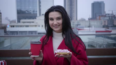kahve molası : Happy young Caucasian woman standing on city street with coffee cup and donut, looking at camera and smiling. Portrait of cheerful girl with black hair and green eyes. Happiness, lifestyle, break.