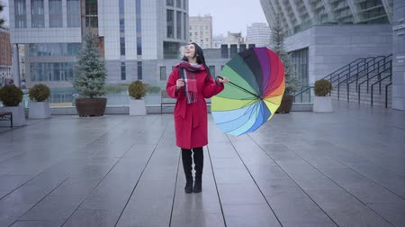 plezant : Long shot of positive young Caucasian woman with multi-colored umbrella spinning on city street. Cheerful girl in stylish red coat smiling to rainy autumn day. Lifestyle, happiness, joy.
