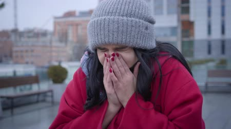 influenza : Close-up portrait of ill Caucasian girl in red coat and warm hat sneezing outdoors. Pretty young woman having flu standing in city. Health care, lifestyle, illness.