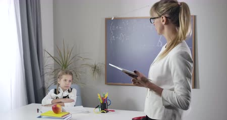 diligence : Positive Caucasian schoolgirl making victory gesture as sitting at the table. Adult female tutor teaching girl at home. Education, happiness, intelligence. Cinema 4k ProRes HQ. Stock Footage