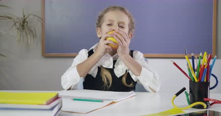 polegar : Charming Caucasian schoolgirl writing in exercise book, biting apple and showing thumb up. Happy female student doing homework. Education concept, intelligence. Cinema 4k ProRes HQ.