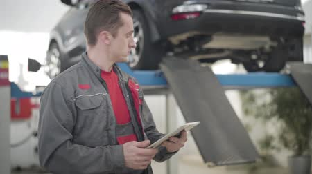autotuning : Portrait of concentrated Caucasian man using tablet and looking back at car in repair shop. Professional male auto mechanic working in auto service station. Industry, insurance, maintenance. Videos