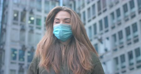 mortality : Portrait of beautiful Caucasian woman with grey eyes wearing protective mask in city. Young girl standing at the background of buildings. Coronavirus, covid-19, global problem. Cinema 4k ProRes HQ. Stock Footage