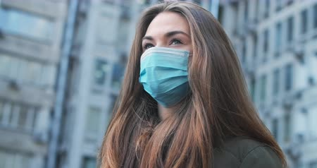 dünya çapında : Bottom side view of exhausted brunette woman in protective mask standing outdoors. Close-up of young Caucasian girl taking safety measures against Covid-19. Cinema 4k ProRes HQ. Stok Video