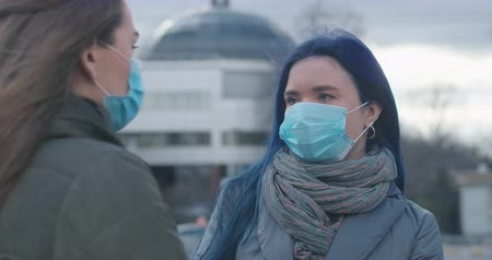mortality : Close-up portrait of young woman in protective mask standing on city street and talking with unrecognizable female friend at the foreground. Girls discussing Covid-19 outdoors. Cinema 4k ProRes HQ. Stock Footage