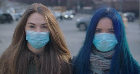 mortality : Close-up faces of two young women in protective masks looking at camera at the background of busy city street. Portrait of worried girls outdoors. Epidemic, Covid-19, illness. Cinema 4k ProRes HQ.