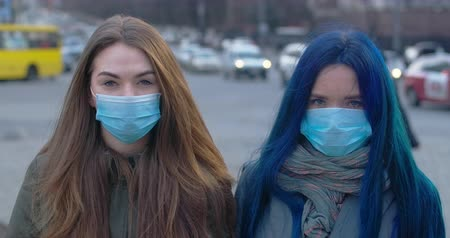 mortality : Portrait of brunette and blue-haired girls wearing protective masks. Young women standing outdoors in the city and looking at camera. Cinema 4k ProRes HQ.