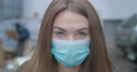 mortality : Close-up face of girl in protective mask looking at camera. Young beautiful brunette woman with grey eyes outdoors in city. Pandemic, medicine, Covid-19. Cinema 4k ProRes HQ. Stock Footage