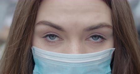 mortality : Close-up of grey eyes of young woman in protective mask looking at camera. Portrait of brunette beautiful girl outdoors. Epidemic, health care, Covid-19. Cinema 4k ProRes HQ. Stock Footage