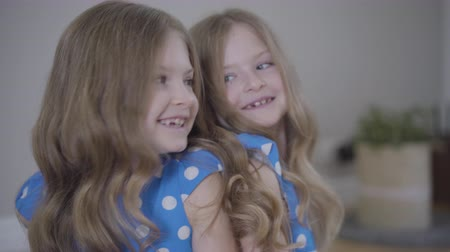 identical : Camera approaching to faces of two identical twin sisters talking and laughing. Brunette cheerful girls in blue dotted dresses resting together at home. Family, lifestyle, unity.