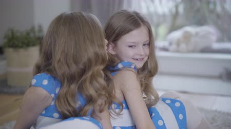 união europeia : Cute Caucasian brunette girl in blue dotted dress smiling as listening to twin sister whispering on her ear. Joyful children spending time together indoors. Happiness, unity, lifestyle. Stock Footage