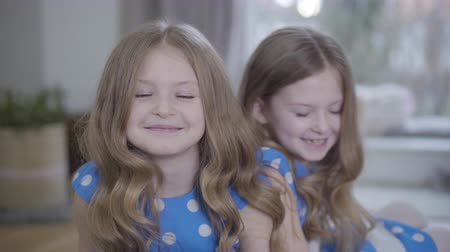 identical : Portrait of pretty little Caucasian brunette girl with grey eyes looking at camera and smiling. Her twin sister sitting at the background and talking with sibling. Joy, happiness, unity, lifestyle. Stock Footage