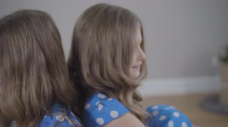 união europeia : Camera moving from left to right around two identical twin sisters in similar blue dotted dresses. Brunette sisters with grey eyes posing indoors on weekends. Unity, happiness, lifestyle. Stock Footage