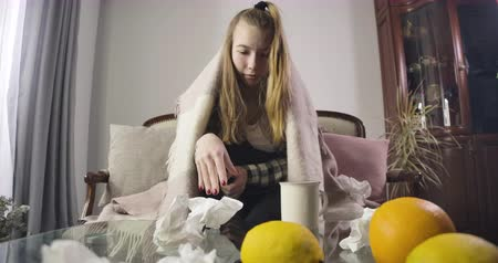 respiratory infection : Portrait of upset Caucasian girl sneezing and drinking hot tea. Oranges and used napkins scattered on the table in front of ill teenager. Fever, runny nose, illness. Cinema 4k ProRes HQ.