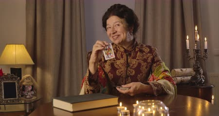 mystik : Mature Caucasian woman raising up jack of hearts, smiling and talking. Happy senior female fortune teller sitting at the table and reading future. Cinema 4k ProRes HQ.