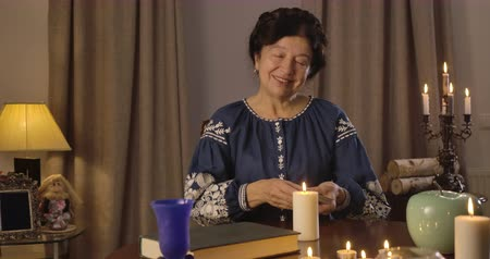 mystik : Portrait of old Caucasian woman in blue blouse sitting at the table with candles and shuffling cards. Smiling witch putting cards on table and talking. Foretelling, augury, mystic. Cinema 4k ProRes HQ