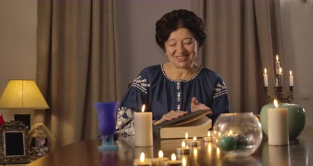 mystik : Portrait of senior brunette Caucasian woman opening vintage book. Mature magician sitting at the table with candles and telling fortune. Augury, divination, fate. Cinema 4k ProRes HQ.