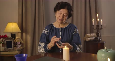 prophète : Camera moving from left to right around mature Caucasian woman shuffling cards at the table. Mature witch talking with cards, lighting candle standing at the foreground. Cinema 4k ProRes HQ.
