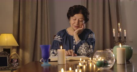 mystik : Portrait of old Caucasian brunette woman sitting at the table with lighting candles and reading. Clairvoyant predicting future with the use of vintage book. Cinema 4k ProRes HQ. Dostupné videozáznamy